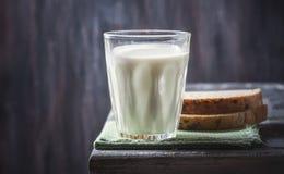 Exponeringsglas av mjölkar med bröd på lantlig träplankabakgrund Royaltyfri Bild