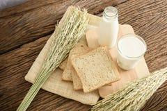 Exponeringsglas av mjölkar och bröd för helt vete på träbrädet royaltyfria foton