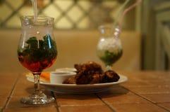 2 exponeringsglas av mojito och grillade fega vingar Royaltyfri Fotografi