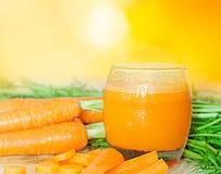 Exponeringsglas av morotfruktsaft med grönsaker på tabell- och apelsinbakgrund Royaltyfri Fotografi
