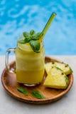 Exponeringsglas av ny ananasfruktsaft med gult glass sugrör, på den mörka träplattan, tjänade som med två stycken av ananas- och  Royaltyfria Foton