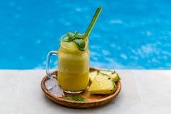 Exponeringsglas av ny ananasfruktsaft med gult glass sugrör, på den mörka träplattan, tjänade som med två stycken av ananas- och  Royaltyfri Bild