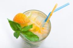 Exponeringsglas av ny lemonad med apelsinen, iskuber, mintkaramell, sugrör Royaltyfria Bilder