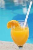 Exponeringsglas av ny orange fruktsaft nära pölen Arkivbild