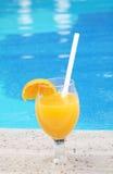 Exponeringsglas av ny orange fruktsaft nära pölen Fotografering för Bildbyråer