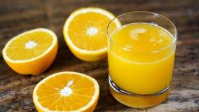 Exponeringsglas av ny orange fruktsaft och klippta apelsiner Arkivbilder