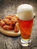 Exponeringsglas av nya öl- och stekt kycklingvingar royaltyfria foton