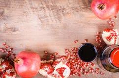 Exponeringsglas av nya granatäpplefruktsaft, frö och frukter på trä Royaltyfri Foto