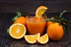 Exponeringsglas av nya orange fruktsaft och apelsiner på träbakgrund Arkivbilder