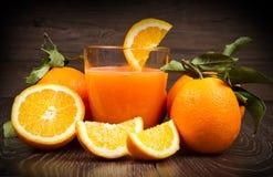 Exponeringsglas av nya orange fruktsaft och apelsiner på träbakgrund Royaltyfri Foto