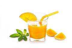 Exponeringsglas av nytt orange fruktsaft och sugrör med mintkaramellen på vit bakgrund Arkivfoto