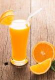 Exponeringsglas av nytt pressande orange fruktsaft med den skivade apelsinen Royaltyfria Bilder