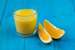 Exponeringsglas av nytt sammanpressad orange fruktsaft och två skivor av apelsin Royaltyfria Foton