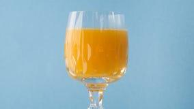 Exponeringsglas av orange fruktsaft med blå bakgrund Royaltyfria Foton