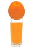 Exponeringsglas av orange fruktsaft med den gula apelsinen överst Fotografering för Bildbyråer