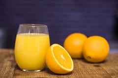 Exponeringsglas av orange fruktsaft med halva en apelsin Arkivfoton