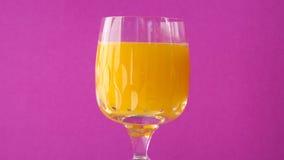 Exponeringsglas av orange fruktsaft med rosa bakgrund Fotografering för Bildbyråer