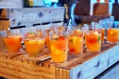 Exponeringsglas av orange fruktsaft med skivad frukt förbereder sig för att tjäna som Royaltyfri Bild