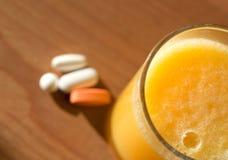 Exponeringsglas av orange fruktsaft med vitaminer på en träyttersida Arkivbild