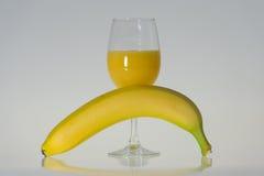 Exponeringsglas av orange fruktsaft och banan Royaltyfri Bild