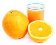 Exponeringsglas av orange fruktsaft och en isolerad halva av frukt Arkivbild