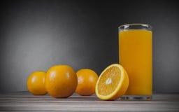 Exponeringsglas av orange fruktsaft och nya apelsiner Arkivfoton