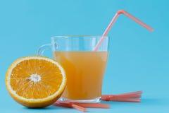 Exponeringsglas av orange fruktsaft och nya apelsiner Arkivfoto