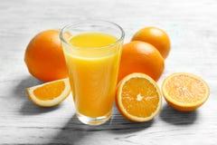 Exponeringsglas av orange fruktsaft och nya frukter royaltyfria bilder