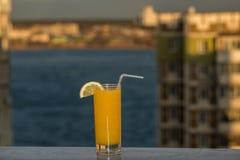 Exponeringsglas av orange fruktsaft på bakgrunden av stadslandskapet Royaltyfria Bilder