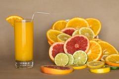 Exponeringsglas av orange fruktsaft på den pappers- bakgrunden med skivor av citruns royaltyfri bild