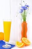 Exponeringsglas av orange fruktsaft på en ljus träbakgrund Royaltyfri Foto