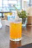 Exponeringsglas av orange fruktsaft på mattabellen Arkivfoton