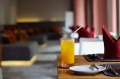 Exponeringsglas av orange fruktsaft på tabellen Arkivbild