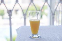 Exponeringsglas av orange fruktsaft på tabellen med den vita bordduken på Arkivfoto