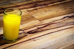 Exponeringsglas av orange fruktsaft på trätabellen Arkivbilder