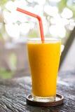 Exponeringsglas av orange fruktsaft på trätabellen Arkivfoto