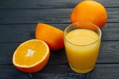 Exponeringsglas av orange fruktsaft på trätabellen, på wood växtbakgrund, ny drink Arkivbilder