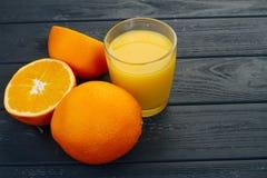 Exponeringsglas av orange fruktsaft på trätabellen, på wood växtbakgrund, ny drink Royaltyfri Fotografi