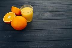 Exponeringsglas av orange fruktsaft på trätabellen, på wood växtbakgrund, ny drink Royaltyfri Bild
