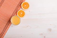 Exponeringsglas av orange ny fruktsaft på en ljus tabell- och apelsinöraöverkant Royaltyfri Foto