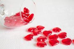 Exponeringsglas av röda hjärtor på en vit bakgrund Arkivbild