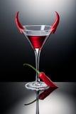 Exponeringsglas av röda martini dekorerade med chilipeppar Arkivfoton