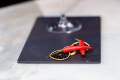 Exponeringsglas av röda martini dekorerade med chilipeppar på stenen royaltyfria foton