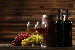 Exponeringsglas av rött och vitt vin med druvor på brun träbakgrund Royaltyfri Bild
