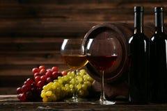 Exponeringsglas av rött och vitt vin med druvor på brun träbakgrund Royaltyfria Bilder