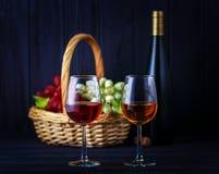 Exponeringsglas av rött och vitt vin med en defocused flaska och frukter Royaltyfria Bilder
