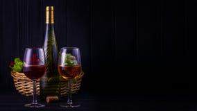 Exponeringsglas av rött och vitt vin med en flaska och frukter Fotografering för Bildbyråer