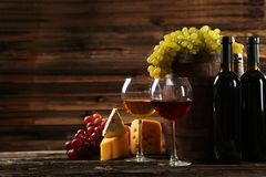 Exponeringsglas av rött och vitt vin, ostar och druvor på brun träbakgrund Arkivbild