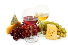 Exponeringsglas av rött och vitt vin, ostar och druvor som isoleras på en vit Arkivbilder