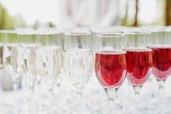 Exponeringsglas av rött och vitt vin på en tabell Många glass vin i rad på den vita bordduken Arkivfoto